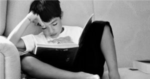 Boy sitting on couch reading